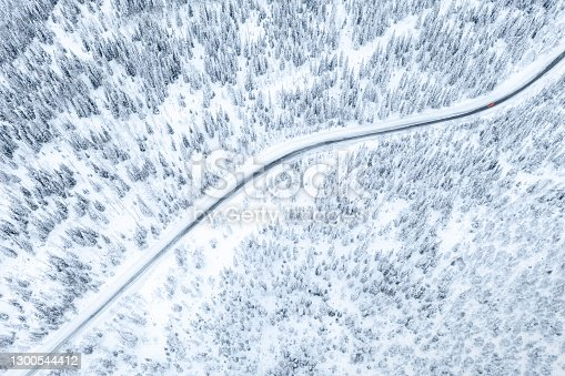 istock Aerial drone view of road in winter forest with red car 1300544412