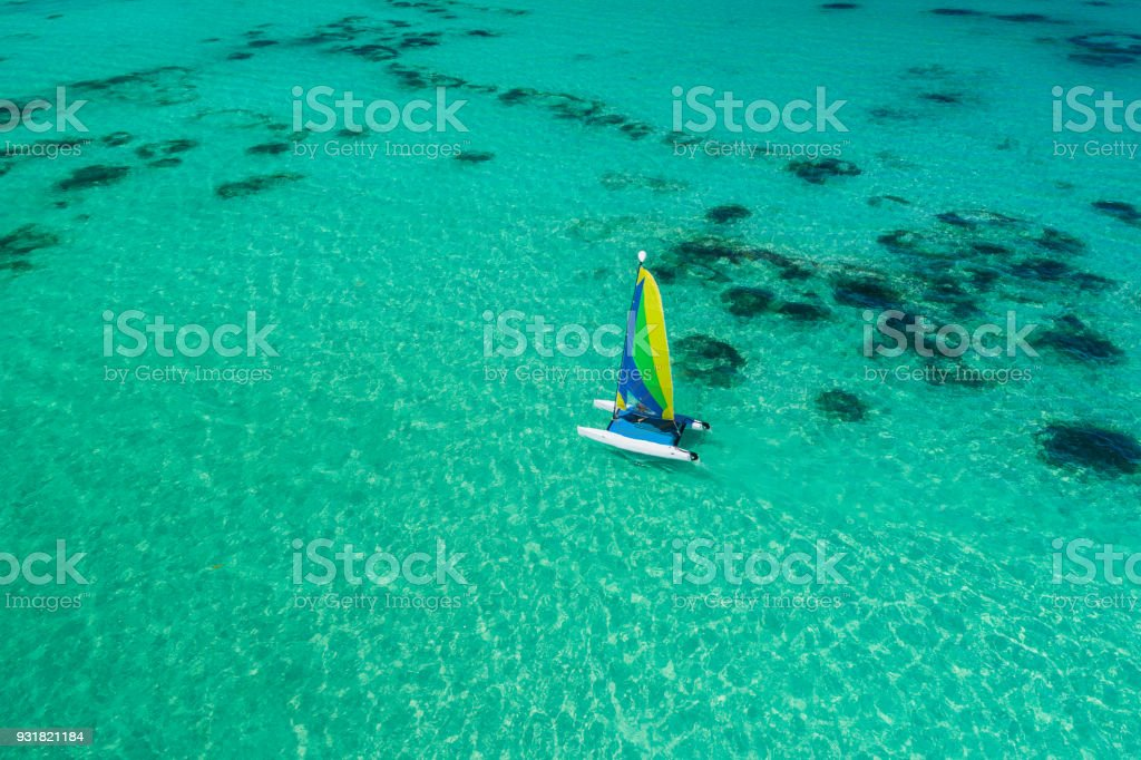 Aerial drone view of sailing sailboat surf or catamaran in turquoise water of Caribbean sea near Punta Cana beach. stock photo