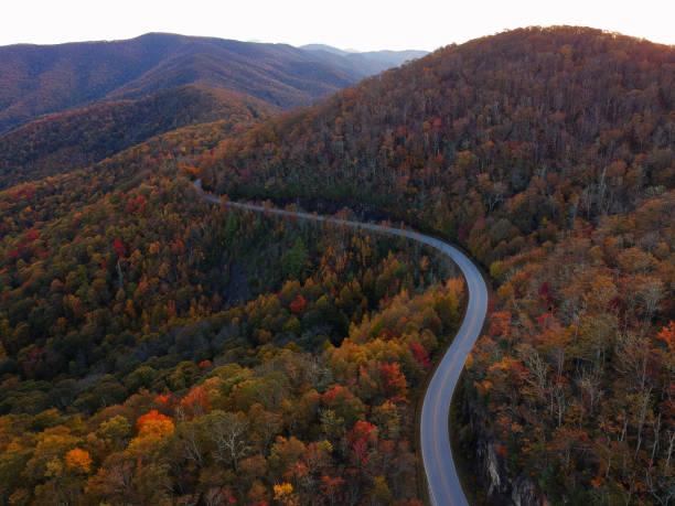 luchtfoto drone bekijken van winding road via herfst / vallen in de blue ridge van de appalachian bergen in de buurt van asheville, north carolina. levendige rode, gele, oranje blad gebladerte kleuren op de curve van de berg straatkant. - zuidoost stockfoto's en -beelden