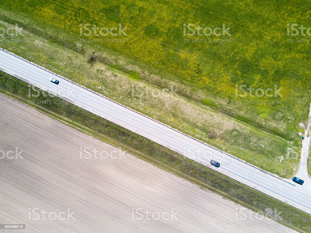 Aerial drone view on the road in the field. On the one hand the opened earth, with another a grass - Zbiór zdjęć royalty-free (Bez ludzi)