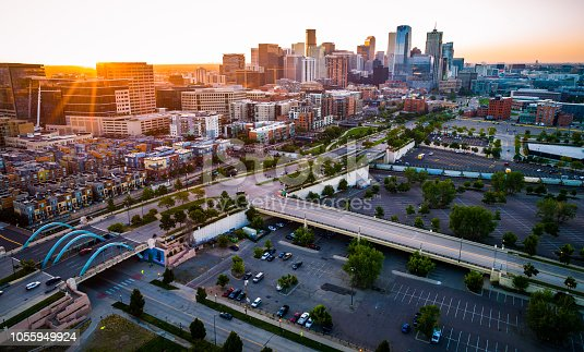 Perfect Golden Hour landscape of the growing modern city of Denver , bridges and highways and newly developed cityscape , aerial drone view Sun beams and Sun rays beaming across horizon in Perfect Denver Colorado Skyline Cityscape high above Mile High City