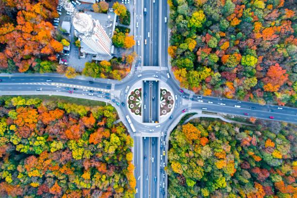 vue aérienne eagle eye d'un rond-point rond-point situé entre la belle forêt d'automne - rond point carrefour photos et images de collection
