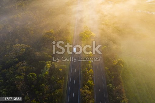 istock Aerial - Fog over Country Road in Victoria Australia on Sunrise 1172710364