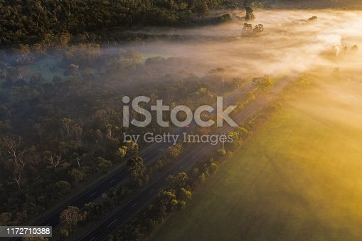 Early morning aerial photograph capturing a car driving down a fog filled road in Victoria, Australia.