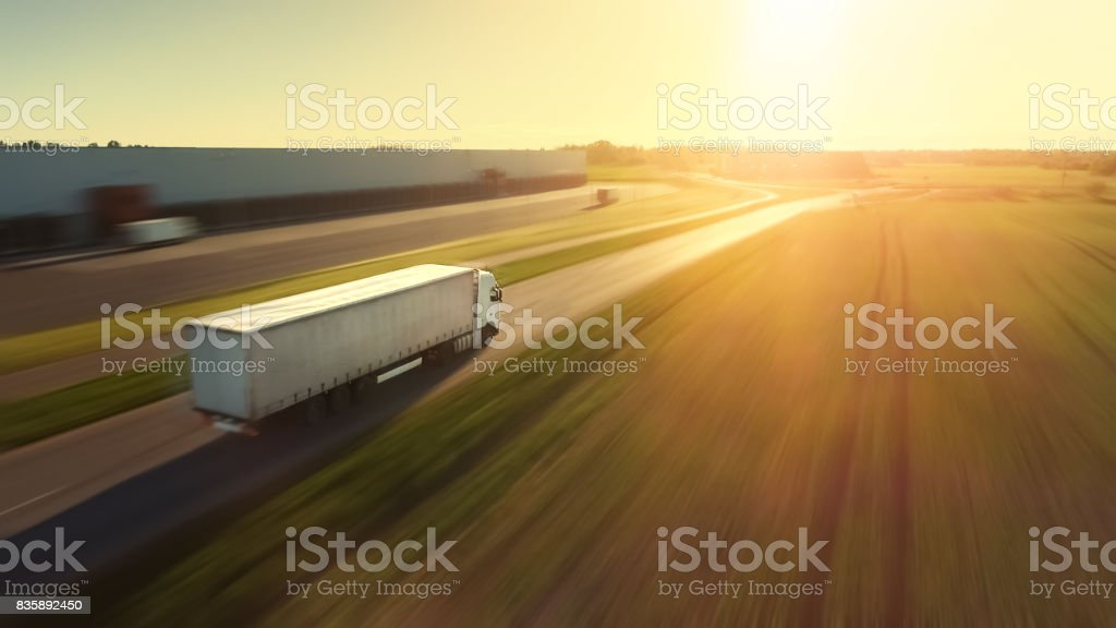 Luftaufnahme der Folgen des weißen Sattelschlepper mit Cargo Trailer befestigt Bewegung durch Industriehalle, ländlichen Gegend. Sonne scheint und der Himmel ist blau. Motion blur. – Foto