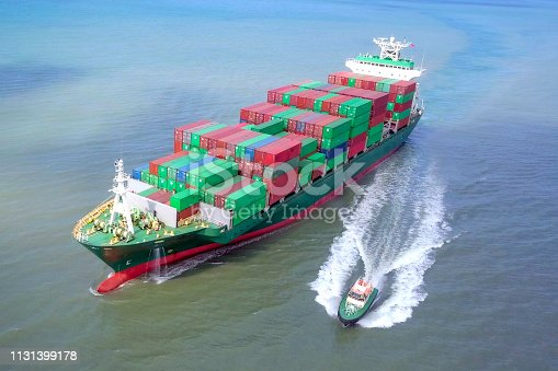 Aerial footage of a pilot boat leaving a container ship at sea, loaded with various container brands.