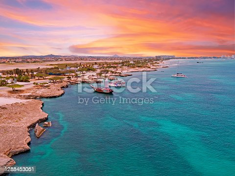 istock Aerial from Aruba island with Palm Beach in the Caribbean Sea at sunset 1288453051