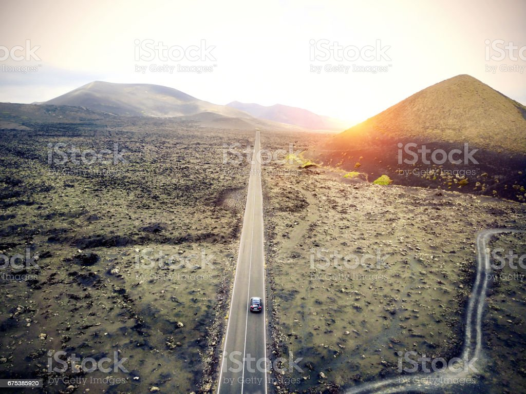 Aerial image of a car driving through a road in Lanzarote, Spain. stock photo