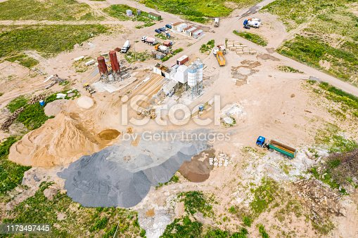 istock aerial image of city construction site. cement processing facility and various building machines 1173497445
