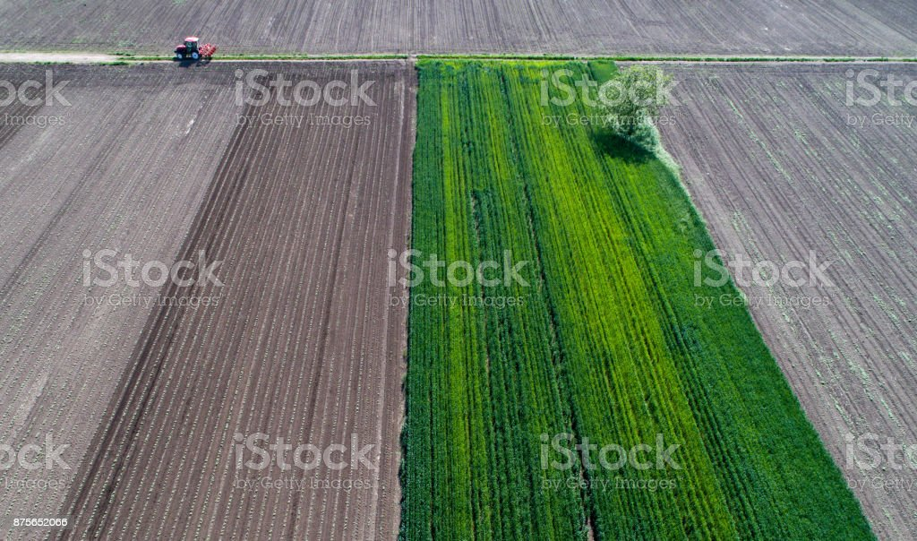 Aerial image of tractor hoeing field stock photo
