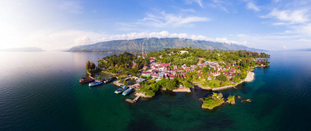 Aerial: lake Toba and Samosir Island view from above Sumatra Indonesia. Huge volcanic caldera covered by water, traditional Batak villages, green rice paddies, equatorial forest. stock photo