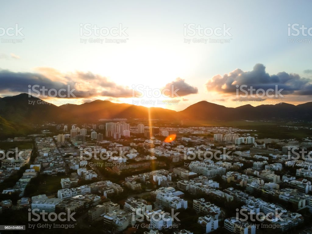 aerial landscape photo of Recreio dos Bandeirantes beach during sunset, with the sun dipping behind the mountains and causing lens orange lens flare - Zbiór zdjęć royalty-free (Bez ludzi)