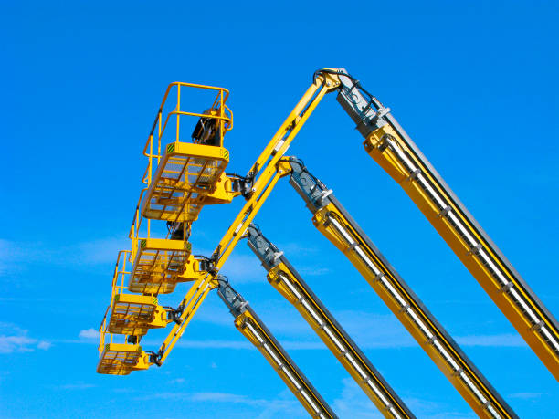 Aerial lifting platforms in the sky Aerial lifting platforms of yellow color in blue sky in a row. retrieving stock pictures, royalty-free photos & images