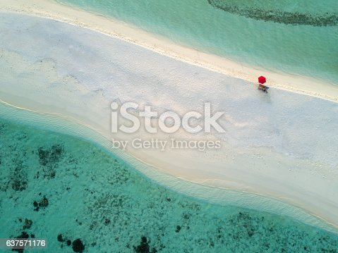 Lonely red umbrella at the beautiful beach of a small tiny  Islet in the South Ari Atoll Area. Aerial Drone 90 Degrees Down View. South Ari Atoll, Republic of Maldives