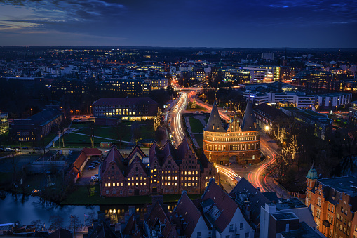 Aerial night view of the illuminated city of Luebeck, Germany in winter with Holstentor and historic Salzspeicher houses, long term exposure at blue hour, copy space