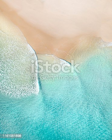 Aerial of a beach with beautiful waves, white sand and ocean textures at sunrise