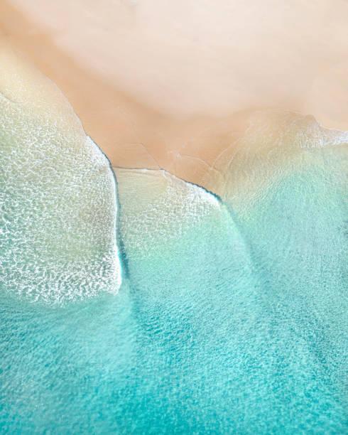 aerial de una playa con hermosas olas, arena blanca y texturas oceánicas - playa fotografías e imágenes de stock
