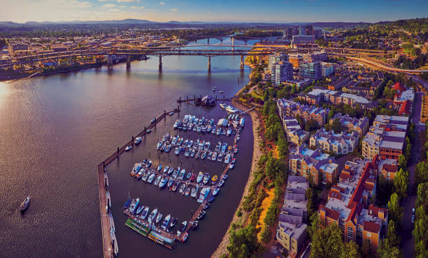 Aerial of Downtown Portland at Tom McCall Waterfront Park overlooking the Marina on early sunny morning with Tilikum Crossing Bridge in the distance stock photo
