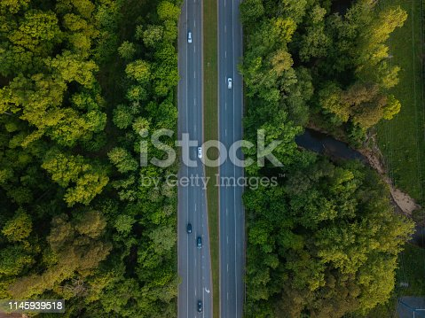 1042711480 istock photo Aerial of Highway through Forest in the Spring 1145939518