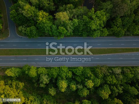 1042711480 istock photo Aerial of Highway through Forest in the Spring 1145939528