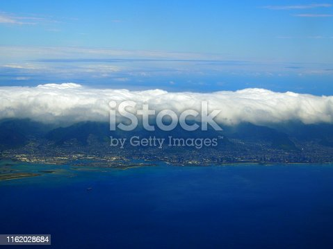 Aerial of Honolulu with clouds hovering above, Waikiki, Buildings, parks, hotels and Condos with Pacific Ocean stretching into the distance on nice day.
