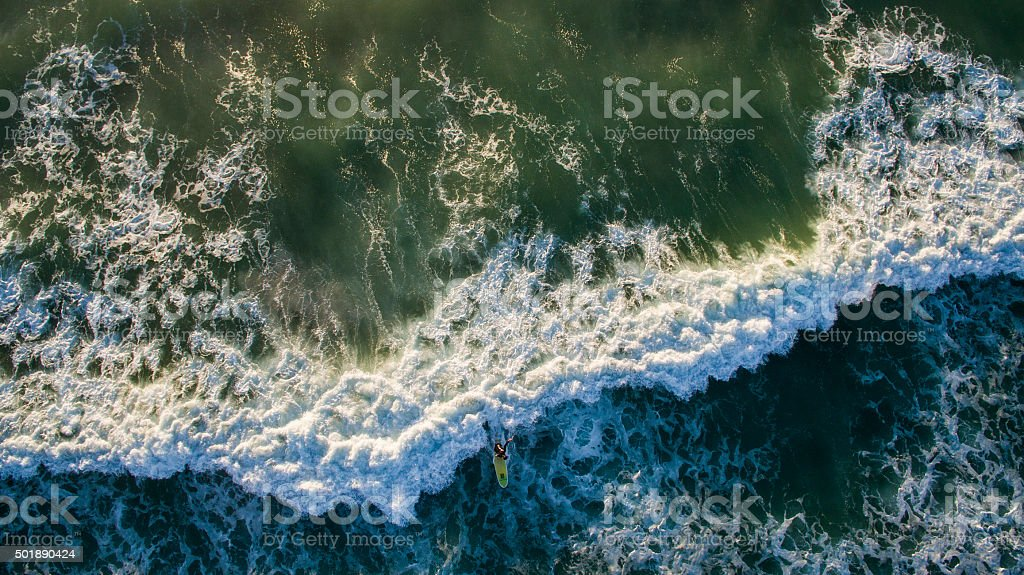Aerial of surfer riding a wave stock photo