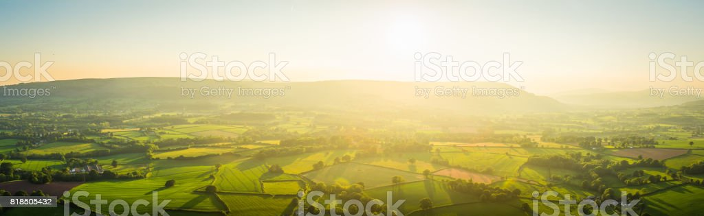 Aerial panorama golden light over idyllic green pasture misty mountains stock photo