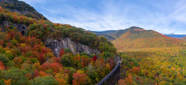 Aerial panorama of fall foliage in the White Mountains Autumn fall colors in Crawford Notch State Park. HDR drone pano shot with train tracks in foreground with forest stretching into distance and up mountains. white mountains new hampshire stock pictures, royalty-free photos & images