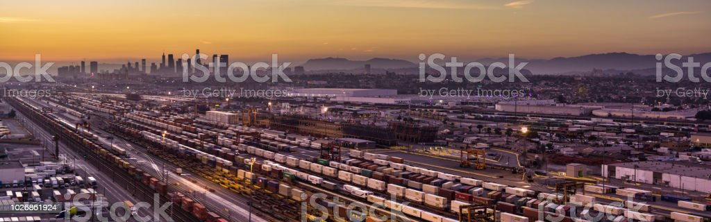 Aerial Panorama of Floodlit Freight Train Yard in Vernon with Downtown LA Skyline at Sunset stock photo