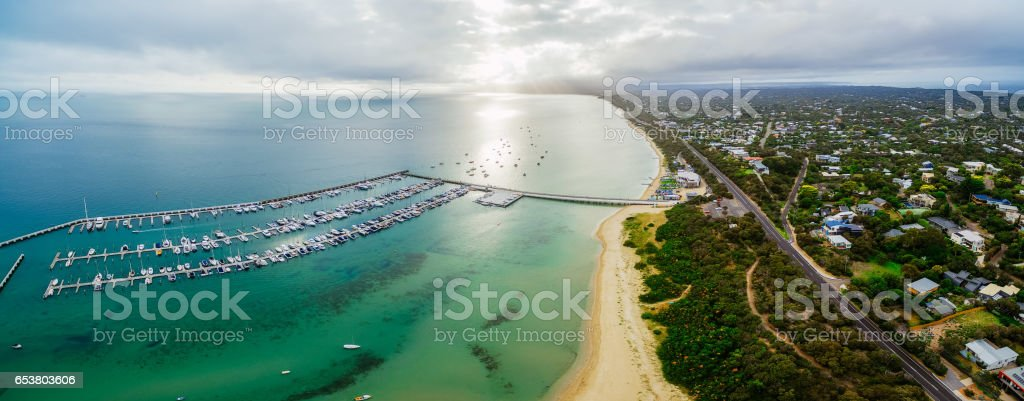 Aerial panorama of land and sea. Long pier and yachts moored at marina near the beach stock photo