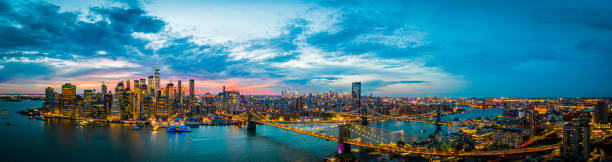 Aerial Panorama of New York Skyline at Night An aerial panoramic image of the Manhattan skyline at night in New York. urban sprawl stock pictures, royalty-free photos & images