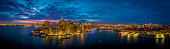 An aerial panoramic image of the Manhattan skyline at night in New York.