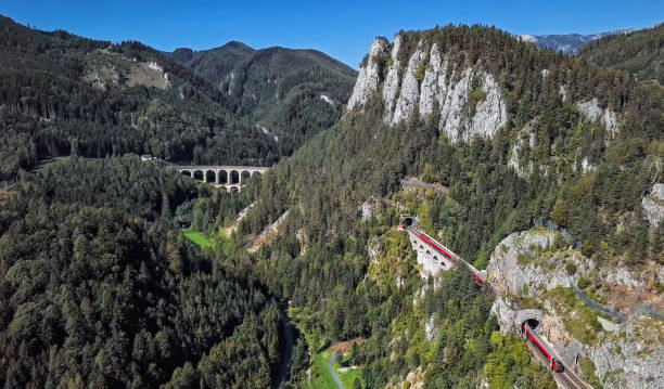 Aerial panorama of red train rides on historical Semmering railway (Semmeringbahn) and famous Kalte Rinne Viaduct, Lower Austria. stock photo