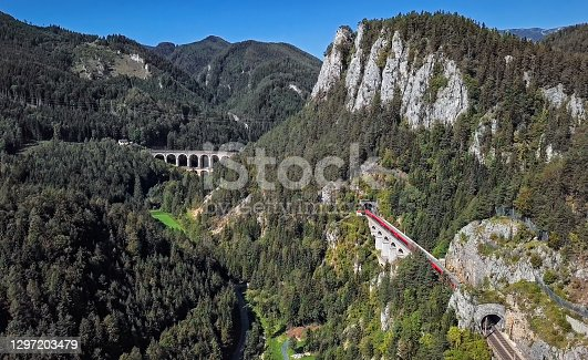 istock Aerial panorama of red train rides on historical Semmering railway (Semmeringbahn) and famous Kalte Rinne Viaduct, Lower Austria. 1297203479