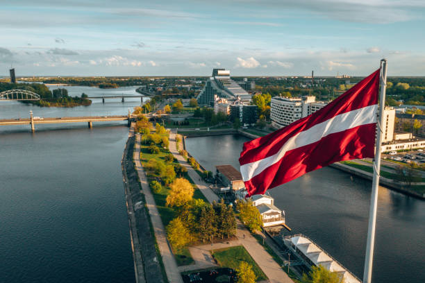 Aerial panorama of Riga city with a big Latvian flag Aerial panorama of Riga city with a big Latvian flag in the foreground. Golden hour. latvia stock pictures, royalty-free photos & images