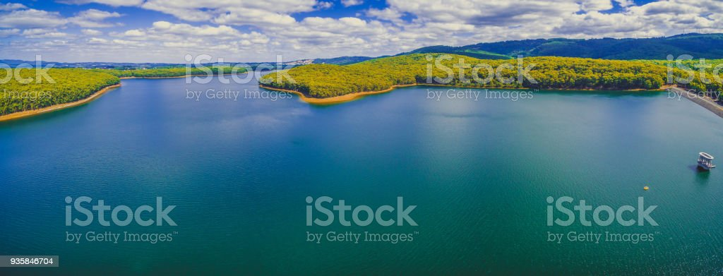 Aerial panorama of Silvan Reservoir lake and forest under fluffy clouds in Melbourne,  Australia stock photo