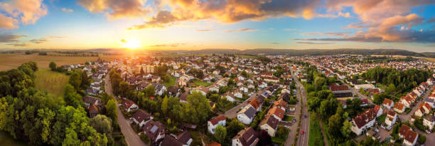 Aerial panorama of small town at sunrise Aerial panorama of a small town at sunrise, with magnificent colorful sky and warm light district stock pictures, royalty-free photos & images