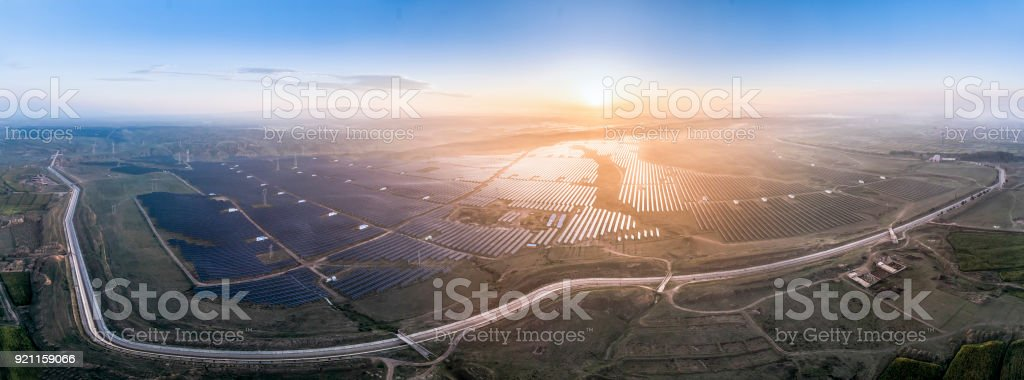 Aerial panorama of solar photovoltaic panels at sunrise stock photo