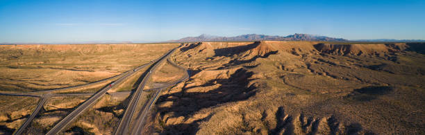 aerial panorama of table mountains in a highland nearby mesquite, nevada, usa, with the rout us-15, in the early springtime. - clark county nevada stock pictures, royalty-free photos & images