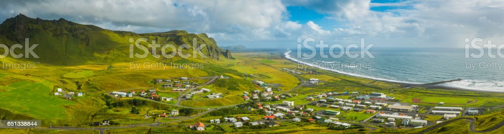 Aerial panorama over coastal village nestled between mountains Vik Iceland stock photo