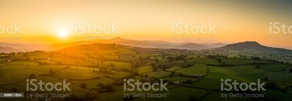 Aerial panorama over golden sunset illuminating picturesque rural farms mountains stock photo