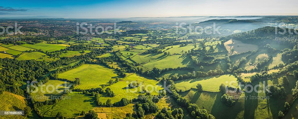 Aerial panorama over green fields misty hills and country town stock photo