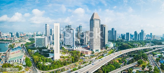 Aerial panorama over the towering skyscrapers and busy highways of downtown Singapore surrounding Marina Bay.