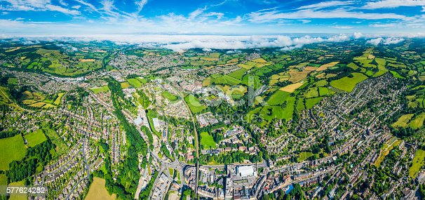Aerial view over homes, streets and suburban community at the edge of picturesque country town surrounded by green pasture and farmland, Stroud, UK. ProPhoto RGB profile for maximum color fidelity and gamut.