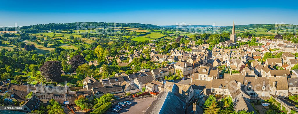 Aerial panorama over idyllic country village cottages green summer fields stock photo
