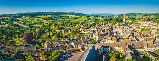 aerial panorama over idyllic country village cottages green summer fields - village stock photos and pictures