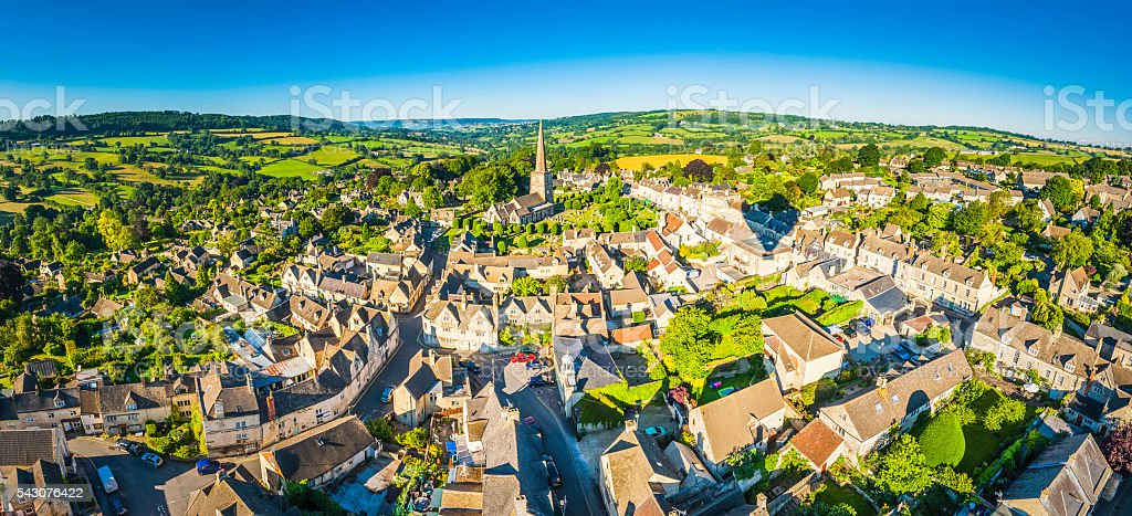 Aerial panorama over idyllic country village cottages patchwork summer landscape stock photo