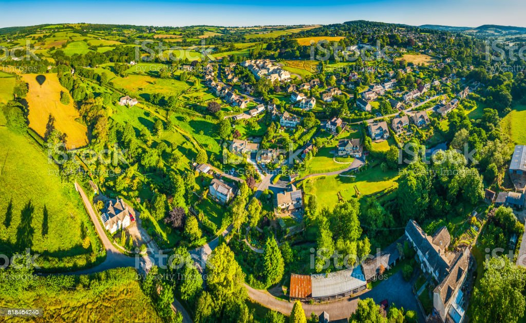 Aerial panorama over idyllic country village homes picturesque summer meadows stock photo