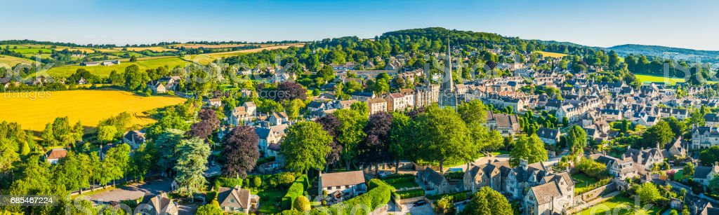 Aerial panorama over idyllic country village homes summer farm fields stock photo