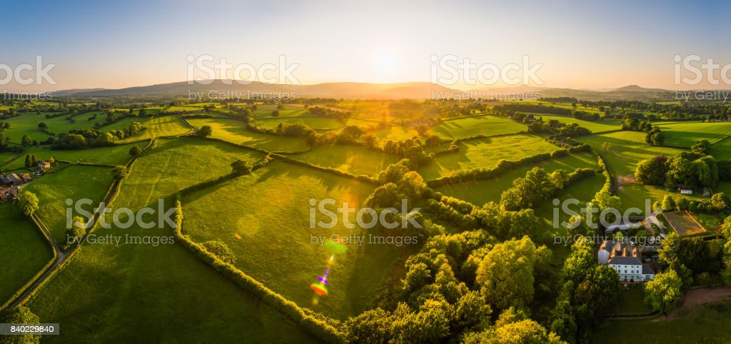 Aerial panorama over idyllic countryside farms fields mountains at sunset stock photo